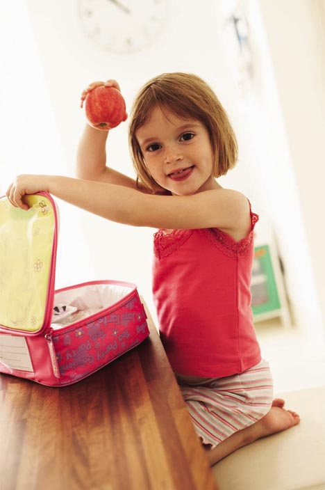 MODEL RELEASED. Packed lunch. Girl holding up an apple from her lunchbox. She is four years old.
